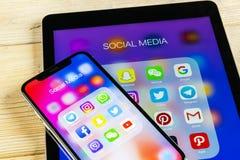 Apple iPhone X och iPad med symboler av social massmediafacebook, instagram, kvittrande, snapchatapplikation på skärmen Social ma Royaltyfri Bild
