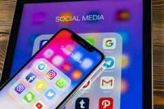 Apple iPhone X och iPad med symboler av social massmediafacebook, instagram, kvittrande, snapchatapplikation på skärmen Social ma Arkivfoton