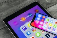 Apple iPhone X och iPad med symboler av social massmediafacebook, instagram, kvittrande, snapchatapplikation på skärmen Social ma Arkivfoto