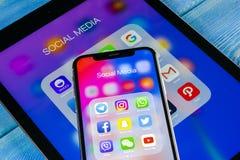 Apple iPhone X och iPad med symboler av social massmediafacebook, instagram, kvittrande, snapchatapplikation på skärmen Social ma Royaltyfri Fotografi