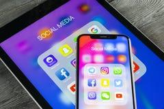 Apple iPhone X och iPad med symboler av social massmediafacebook, instagram, kvittrande, snapchatapplikation på skärmen Social ma Arkivbilder