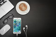 Apple iPhone 8 plus. Kyiv, Ukraine - Fabruary 6, 2018: Apple iPhone 8 plus with coffee cup and MacBook Pro on black table, top view. Apple Inc. is an American Stock Photography