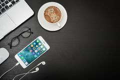 Apple iPhone 8 plus. Kyiv, Ukraine - Fabruary 6, 2018: Apple iPhone 8 plus with coffee cup and MacBook Pro on black table, top view. Apple Inc. is an American Royalty Free Stock Image