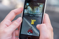 Apple iPhone5s con Pikachu da Pokemon va l'applicazione, mani di un gioco dell'adolescente Immagine Stock Libera da Diritti