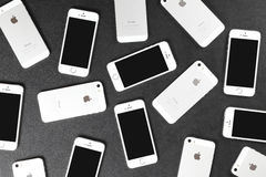 Apple iPhone 5s smartphones lying on leather surface Royalty Free Stock Images