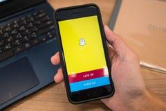 Apple iPhone7 trzymający w jeden ręce pokazuje swój ekran z Snapchat zastosowaniem zdjęcie stock