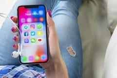 Apple-iPhone X in vrouwenhanden met pictogrammen van sociale media facebook, instagram, tjilpen, snapchat toepassing op het scher Stock Foto's