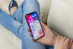 Apple-iPhone X in vrouwenhanden met pictogrammen van sociale media facebook, instagram, tjilpen, snapchat toepassing op het scher Stock Foto