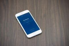 Apple Iphone 6 in witte kleur met facebookpagina die op woode leggen Royalty-vrije Stock Foto's