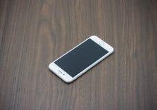 Apple Iphone 6 in witte kleur met het lege scherm die op houten leggen Stock Afbeeldingen