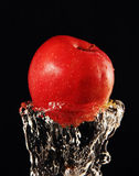 Apple in a jet of water. Royalty Free Stock Images