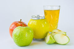 Apple juice. Composition of apples, one of which is in the form of can, and glass of fresh juice Stock Photos