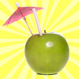 Apple Juice. Concept image of fresh apple juice featuring an apple with a straw and an umbrella in it Royalty Free Stock Photo