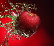 Apple in juice. Red apple in juice stream Stock Image