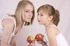 Apple juice. Two girls drinking juice from an apple stock photography