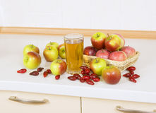 Apple juice with apples and Cornelian cherry on the table. Apple juice in a glass on a table with apples and Cornelian cherry Royalty Free Stock Photo