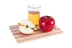 Apple juice and apples. Red apples and glass of juice on cutting board Royalty Free Stock Image