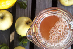 Apple juice. A can full of apple juice, near apples, mint, lemon and lime Stock Images