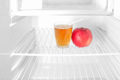Apple and juice in empty refrigerator diet symbol Stock Image