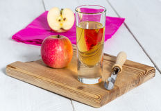Apple juice freshly squeezed in glass on wood Royalty Free Stock Photo
