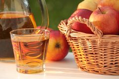 Apple juice. Glass with juice and basket with apples in a garden royalty free stock images