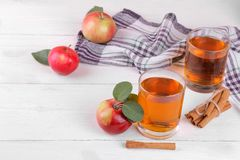 Apple juice in a glass with mature red apples and cinnamon on a white wooden table. Apple juice in a glass with mature fresh red apples and cinnamon on a white royalty free stock photography