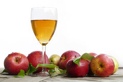 Apple juice in a glass and red apples with leaves on old wood, w Stock Photos