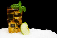 Apple juice,ice cubes and apple with mint on black on snow Royalty Free Stock Photo