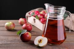 Apple juice in a jug next to red apples on a brown wooden table. Apple juice in a jug next to fresh red apples on a brown wooden table stock photo