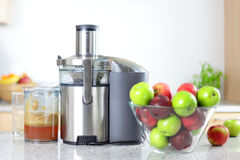Apple juice on juicer machine - juicing Royalty Free Stock Photography