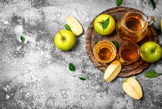 Apple juice in pitcher on the Board with a fresh , green apples. Stock Photos
