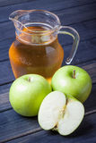 Apple juice in pitcher on table, vertical still life Royalty Free Stock Photos