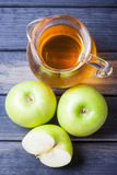 Apple juice in pitcher on table, vertical top view still life Royalty Free Stock Image