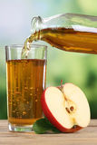Apple juice pouring from apples into a glass Stock Image