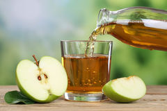 Apple juice pouring from green apples into a glass Royalty Free Stock Image