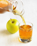 Apple juice pouring from jug into a glass Stock Photos
