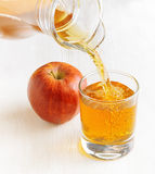 Apple juice pouring from jug into a glass Royalty Free Stock Photos