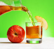 Apple juice pouring from jug into a glass Royalty Free Stock Photography