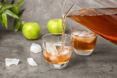 Apple juice pouring from jug into glass with ice cubes. On table Royalty Free Stock Images
