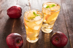 Apple juice pouring from red apples fruits into a glass Royalty Free Stock Photo