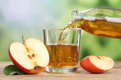 Apple juice pouring from red apples into a glass Stock Photography