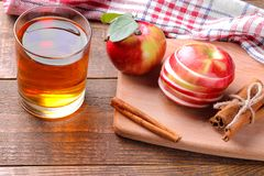 Apple juice with ripe apples and cinnamon sticks on a brown wooden background. Apple juice with fresh ripe apples and cinnamon sticks on a brown wooden stock photo