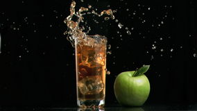 Apple juice splashing in super slow motion because of ice cube stock video footage