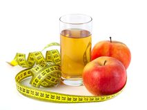 Apple and apple juice with tape measure on white background stock image
