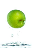 An apple jumping out of the water Stock Photo