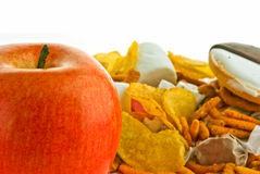 Apple and junk food. A apple and a lot of junk food on white Stock Photography