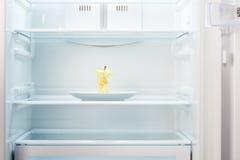Apple kärna på den vita plattan i öppet tomt kylskåp Royaltyfri Foto