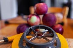 Apple köksredskap som används till att kärna ur frukt med, pyramid av äpplen och skalare som visas på köks tabell royaltyfri foto
