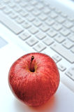 Apple on keyboard. A red apple on a laptop keyboard royalty free stock photography