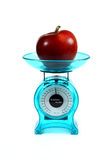 Apple on a kitchen scale Stock Images